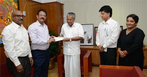 IBS Software Executive Chairman V K Mathews handing over the cheque to Chief Minister Pinarayi Vijayan
